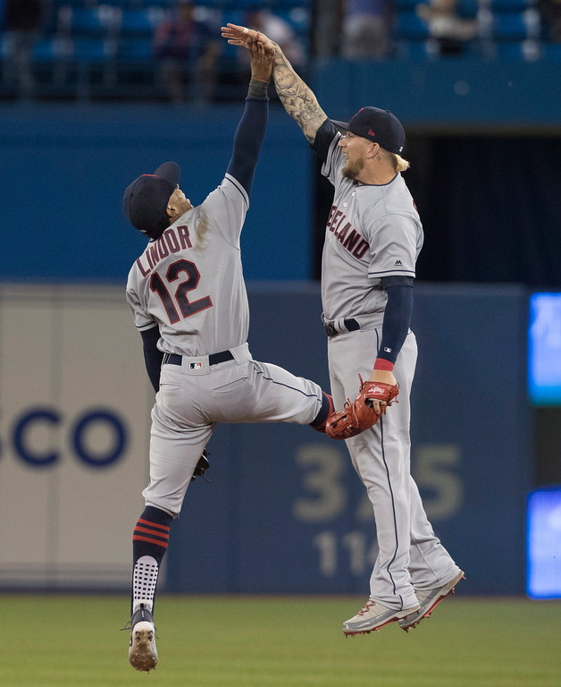 . Cleveland Indians\' Francisco Lindor, left, and Brandon Barnes celebrate the team\'s 9-4 win over the Toronto Blue Jays in a baseball game Thursday, Sept. 6, 2018, in Toronto. (Fred Thornhill/The Canadian Press via AP)