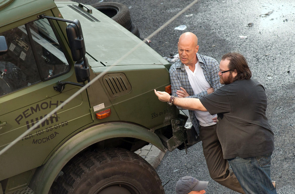 """. In this photo made available Tuesday, June 19, 2012, US actor Bruce Willis playing the role of John McClane, left, listens to Irish director John Moore, right, next to a Russian military jeep during shooting of the movie \""""A Good Day to Die Hard\"""", the fifth part of the \""""Die Hard\"""" series in Budapest, Hungary, Monday, June 18, 2012. (AP Photo/MTI, Bea Kallos)  (Movie released on January 31, 2013)"""