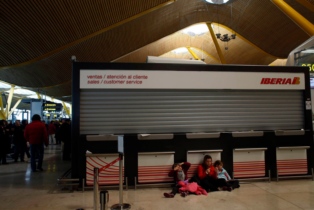 . Passengers sit on the floor as they wait for help after more than 80 Iberia flights were cancelled due to a strike, at Madrid\'s Barajas airport February 18, 2013. Striking union workers clashed with police at the airport on Monday on the first day of a week-long strike over more than 3,800 pending job cuts at Spain\'s flagship airline Iberia. REUTERS/Susana Vera
