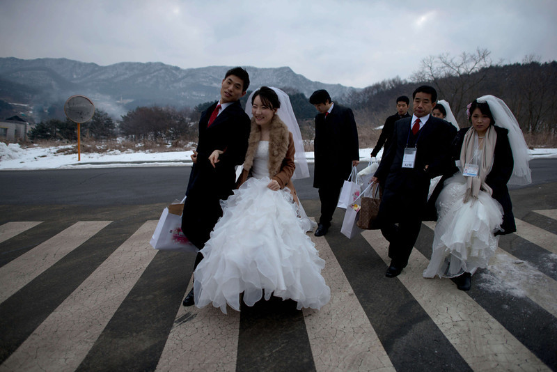 ". Couples arrive for a mass wedding at an event held by the Unification Church in Gapyeong on February 12, 2014. Unification Church members forming 2500 couples from 52 countries were married in a mass wedding in South Korea -- only the second such event since the death of their ""messiah\"" and controversial church founder Sun Myung Moon. (ED JONES/AFP/Getty Images)"