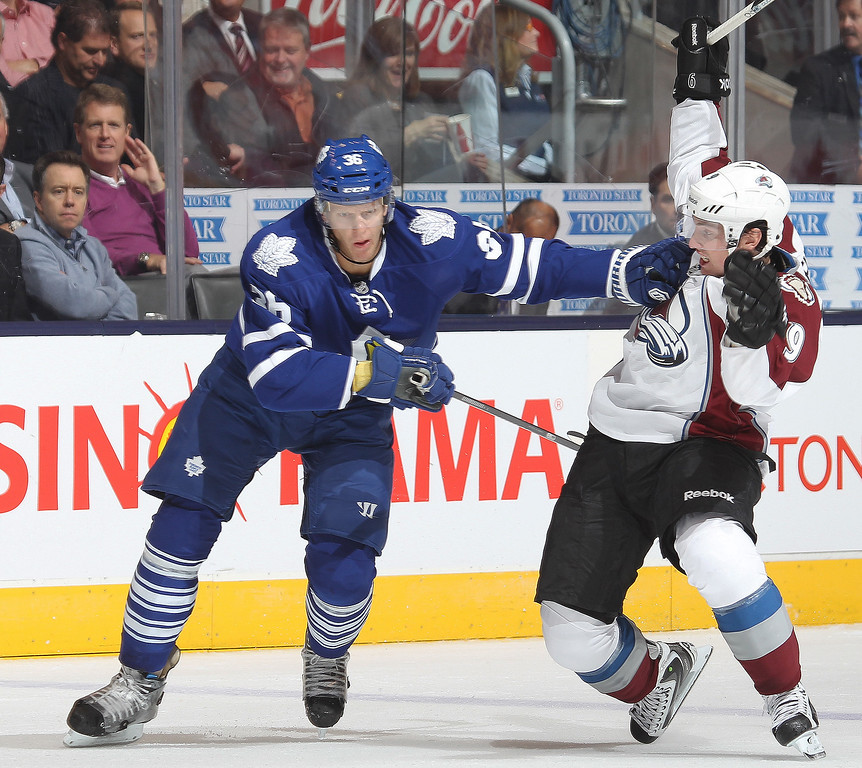 . Matt Duchene #9 of the Colorado Avalanche is held up by Carl Gunnarsson #36 of  the Toronto Maple Leafs during an NHL game at the Air Canada Centre on October 8, 2013 in Toronto, Ontario, Canada. (Photo by Claus Andersen/Getty Images)