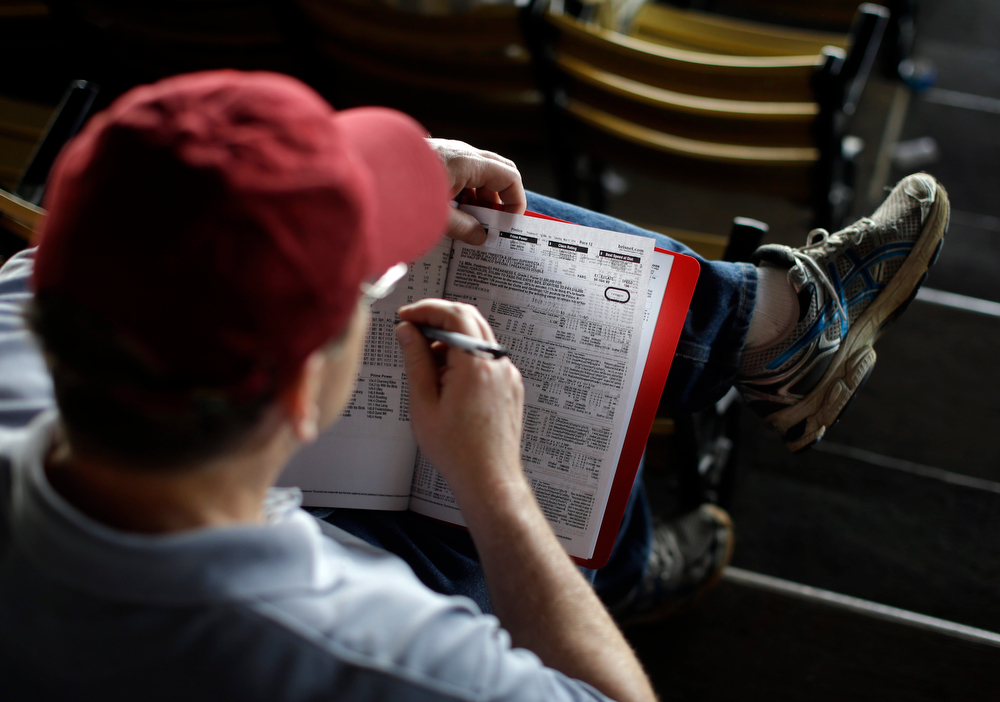 . Greg Cierpial of Linden, N.J., looks through a race program in the grandstand at Pimlico Race Course in Baltimore, Saturday, May 17, 2014, before the 139th running of the Preakness Stakes horse race. (AP Photo/Patrick Semansky)