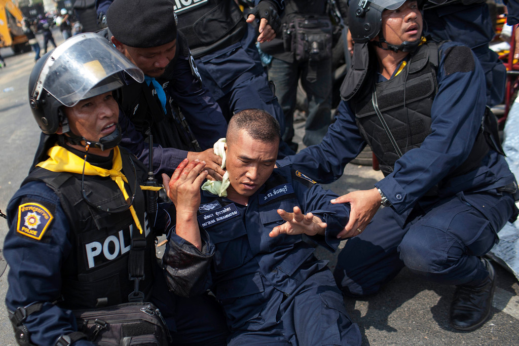 . A police officer (C) injured by a grenade thrown by anti-government protesters during a failed attempt to retake the Phan Fah Bridge is assisted by his fellow officers in Bangkok on February 18, 2014.  AFP PHOTO / KC Ortiz/AFP/Getty Images