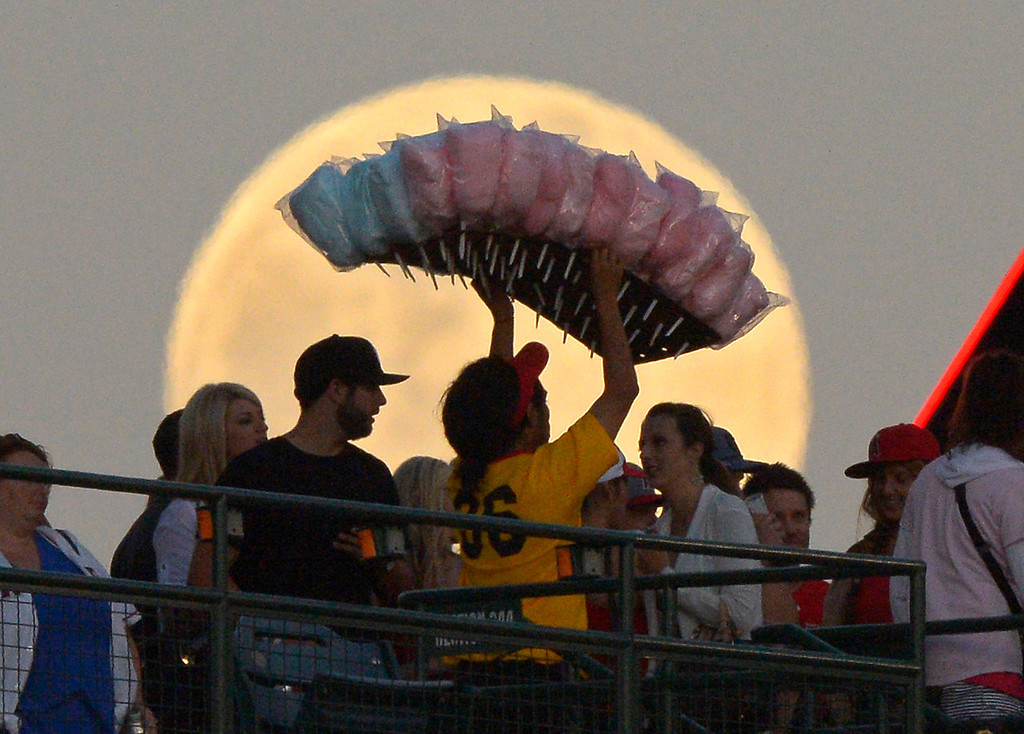 . A cotton candy vendor walks in front of the moon during the Los Angeles Angels\' baseball game against the Pittsburgh Pirates on Saturday, June 22, 2013, in Anaheim, California.  (AP Photo/Mark J. Terrill)