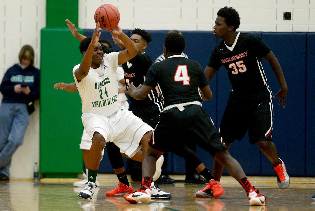 . Tedmund Taylor Jr. (24) of Overland is guarded tightly by Charles Roberts (3) of EagleCrest, Xaiv�ion Jackson (4) and Josh Walton (35) during the first half of play. The Overland Trailblazers hosted the Eaglecrest Raptors on Friday, January 8, 2016. (Photo by AAron Ontiveroz/The Denver Post)