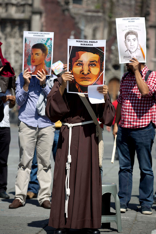 . In this Thursday, Nov. 6, 2014 photo, demonstrators holding posters that show portraits of 3 of the 43 missing rural college students, gather for a prayer during a protest in the Zocalo, Mexico City\'s main square. Suspects in the disappearance of the 43 have confessed to loading the youths onto dump trucks, murdering them at a landfill, then burning the bodies and dumping the ashen remains into a river, Mexican authorities said Friday. (AP Photo/Eduardo Verdugo)