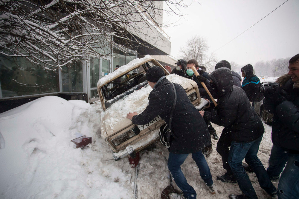 . In this photo taken on Friday, March 15, 2013, members of a pro-Kremlin youth group upturn the car that belongs to pushers of spice, a synthetic drug, in Moscow, Russia. Russian officials and anti-drugs campaigners say that spice has become one of the most dangerous drugs widely available to youngsters and almost impossible to ban because of the constantly changing chemical ingredients. (AP Photo/ Alexander Zemlianichenko Jr)