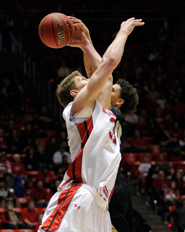 . Utah center Dallin Bachynski, left, and Colorado guard Askia Booker compete for a rebound in the first half during an NCAA college basketball game Saturday, Feb. 2, 2013 in Salt Lake City. (AP Photo/Steve C. Wilson)