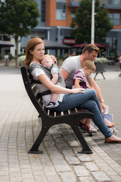 Izmi_Baby_Carrier_Mid_Grey_Lifestyle_Front_Carry_Sitting_On_Bench_Baby_Sleeping.jpg