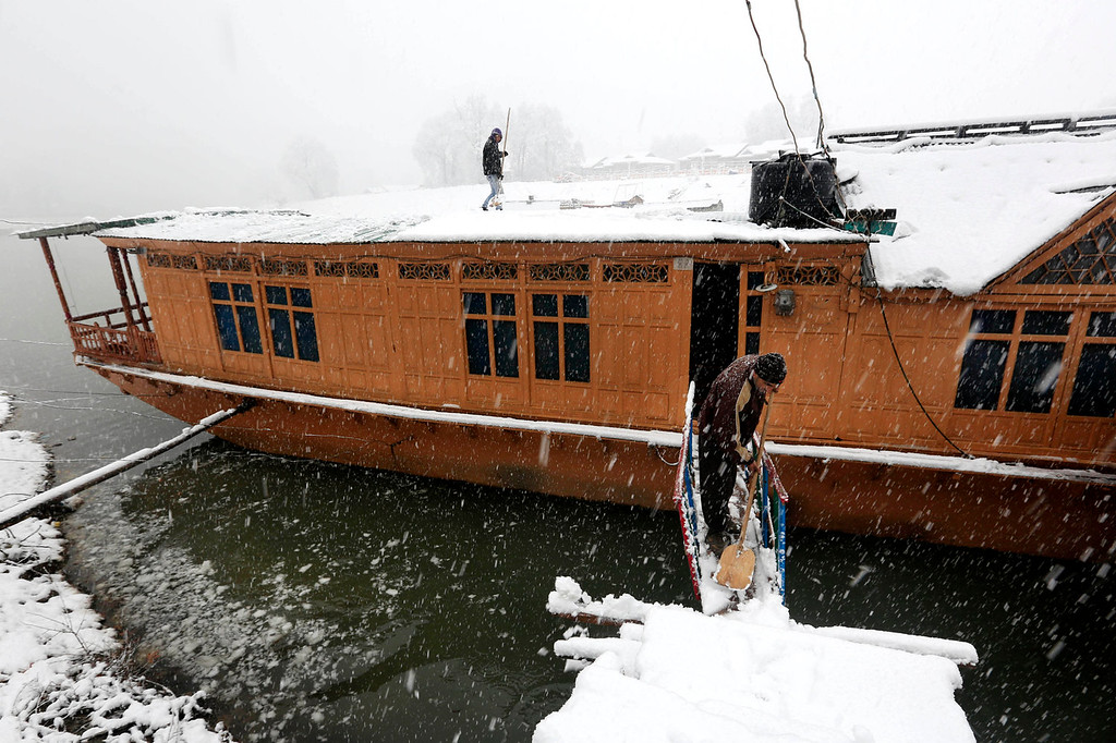 . Kashmiri boat men clear snow from their houseboat during a snowfall in Srinagar, India,  Tuesday, Dec. 31, 2013. Snowfalls in the Indian portion of Kashmir has disrupted power supply,air traffic and road traffic between Srinagar and Jammu, the summer and winter capitals of India\'s Jammu-Kashmir state, according to news reports. (AP Photo/Dar Yasin)