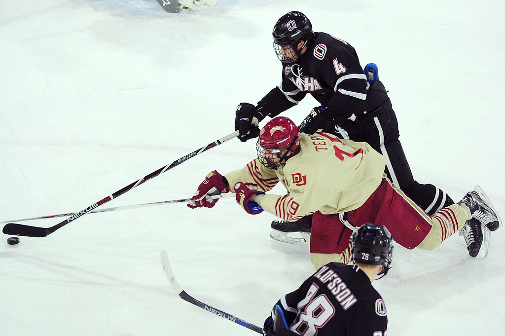 . Denver Pioneers forward Troy Terry (19) dives to steal the puck from Nebraska-Omaha Mavericks defenseman Luc Snuggerud (4) during the third period at Magness Arena on March 4, 2016 in Denver, Colorado. Denver defeated Nebraska-Omaha 3-0. (Photo by Brent Lewis/The Denver Post)