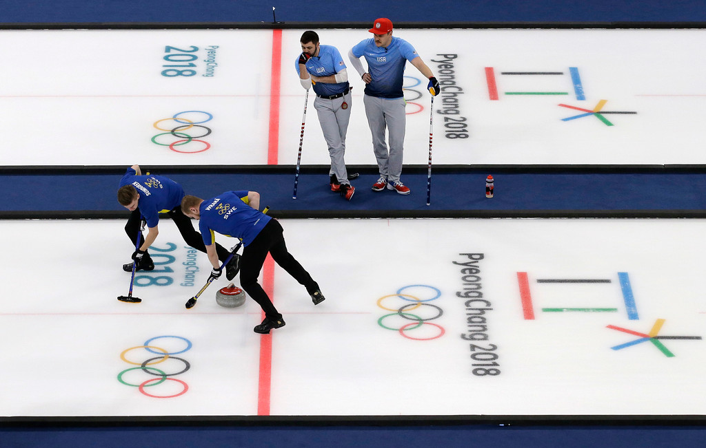 . United States\' Matt Hamilton, right, and John Landsteiner, second from right, looks as the Sweden\'s Christoffer Sundgren, left, and Rasmus Wranaa sweep ice during the men\'s curling finals match at the 2018 Winter Olympics in Gangneung, South Korea, Saturday, Feb. 24, 2018. United States won gold. (AP Photo/Aaron Favila)