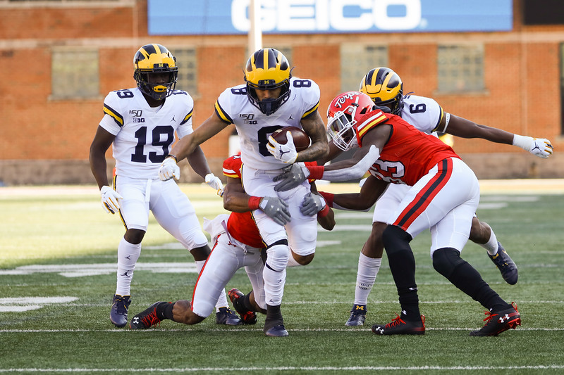 Michigan WR Ronnie Bell is tackled by Maryland defenders.