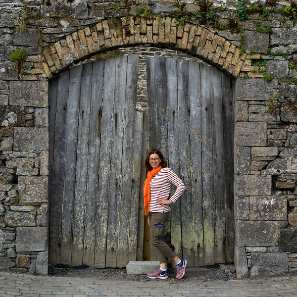 Woman standing against the old wooden door in Killala Town, County Mayo, Ireland