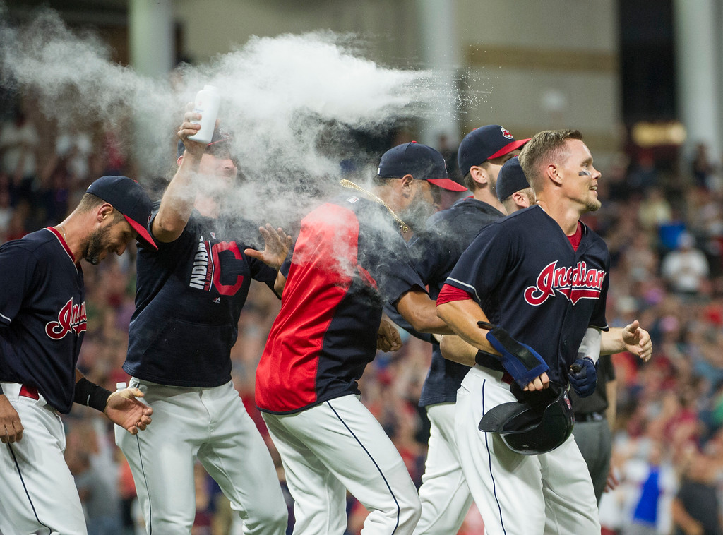 . Cleveland Indians\' Brandon Guyer, right, is mobbed by his teammates after scoring the winning run in the bottom of the ninth inning of a baseball game against the Boston Red Sox in Cleveland, Monday Aug. 21, 2017. (AP Photo/Phil Long)