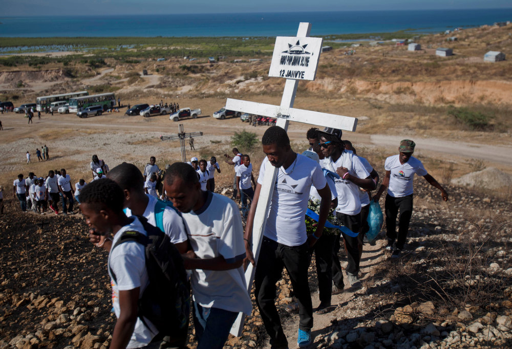 Description of . Relatives of those who died in the 2010 earthquake walk in single file to place a cross on a hilltop to remember those who died in the devastating earthquake, prior to a memorial service at Titanyen, a mass burial site north of Port-au-Prince, Haiti, Saturday, Jan. 12, 2013. Haitians recalled the tens of thousands of people who lost their lives in a the 7.0 magnitude earthquake three years ago, marking the disaster\'s anniversary Saturday with a simple ceremony. Haiti\'s previous presidential administration said 316,000 people were killed but no one really knows how many died.  (AP Photo/Dieu Nalio Chery)