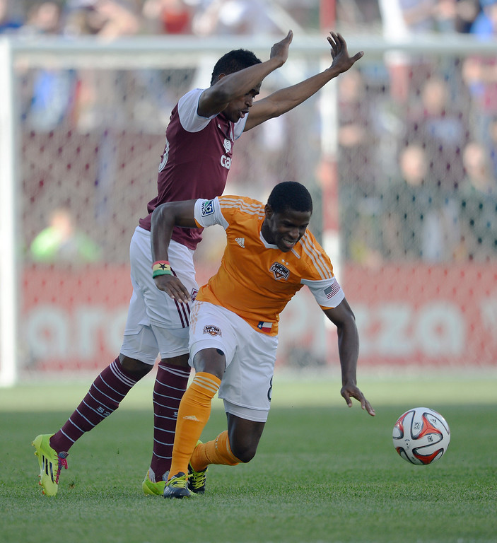 . Colorado Rapids forward Deshorn Brown (26) tries to avoid colliding with Houston Dynamo defender Kofi Sarkodie (8) as he goes after the ball during the first half June 1, 2014 at Dick\'s Sporting Goods Park. (Photo by John Leyba/The Denver Post)