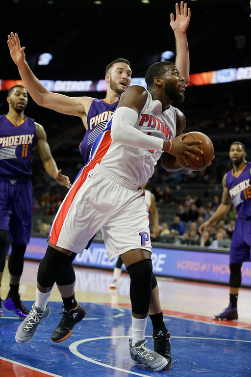 . Detroit Pistons forward Greg Monroe (10) is defended by Phoenix Suns center Miles Plumlee during the first half of an NBA basketball game in Auburn Hills, Mich., Wednesday, Nov. 19, 2014. (AP Photo/Carlos Osorio)