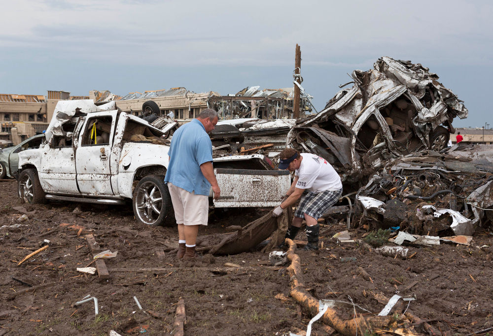 . Two men go through the damage surrounding the Moore Medical Center and damaged vehicals after a tornado moves through Moore, Okla. on Monday, May 20, 2013. (AP Photo/Alonzo Adams)