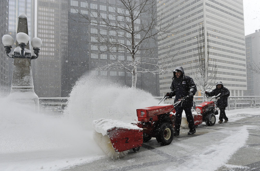 Description of . Arturo Garcia (L) and Ricardo Perez clear snow from Riverside Plaza on March 5, 2013 in Chicago, Illinois. The worst winter storm of the season is expected to dump 7-10 inches of snow on the Chicago area with the worst expected for the evening commute.  (Photo by Brian Kersey/Getty Images)