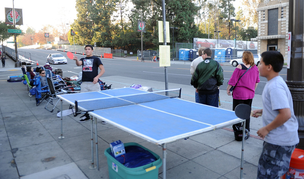 . Fifteen year-old Dallas Teran, left, plays ping pong with tele year-old Devin Teran of Apple Valley as people camp out and stake their spots for the Rose Parade along Colorado Boulevard in Pasadena, Calif., on Tuesday, Dec. 29, 2013.     (Keith Birmingham Pasadena Star-News)