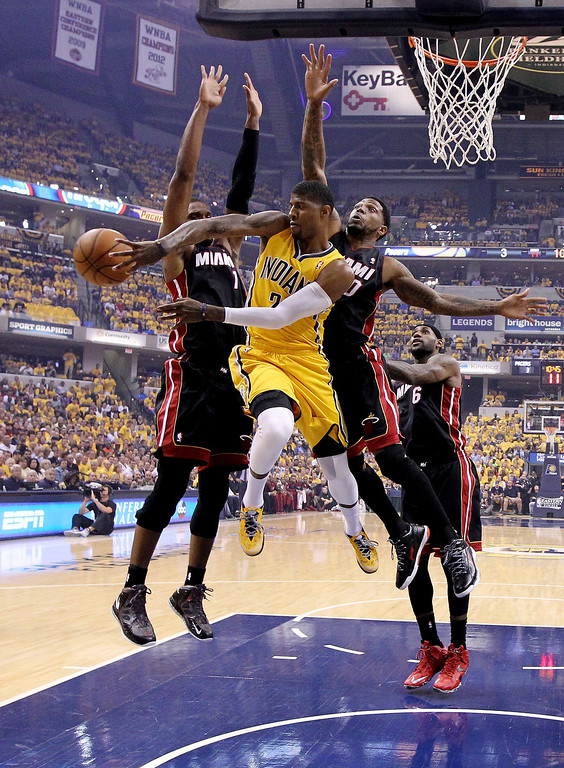 . Paul George #24 of the Indiana Pacers drives to the basket against Chris Bosh #1 and Udonis Haslem #40 of the Miami Heat during Game Two of the Eastern Conference Finals of the 2014 NBA Playoffs at at Bankers Life Fieldhouse on May 20, 2014 in Indianapolis, Indiana.   (Photo by Andy Lyons/Getty Images)