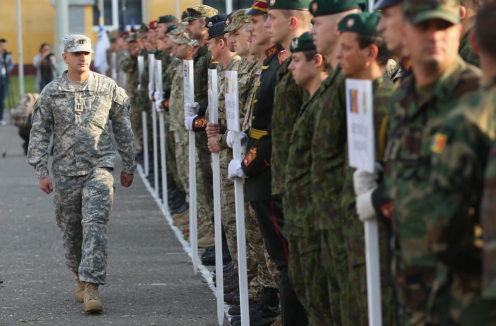 ". A member of the U.S. Army walks past soldiers of different nationalities prior to the opening ceremony of the ""Rapid Trident\"" NATO military exercises on September 15, 2014 near Yavorov, Ukraine.  (Photo by Sean Gallup/Getty Images)"