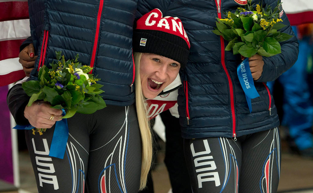 . Canada\'s Kaillie Humphries pokes her head between the silver medallists from the USA after she and Heather Moyse won the gold medal in women\'s bobsled at the Sochi Winter Olympics in Krasnaya Polyana, Russia, Wednesday, Feb. 19, 2014. (AP Photo/The Canadian Press, Jonathan Hayward)