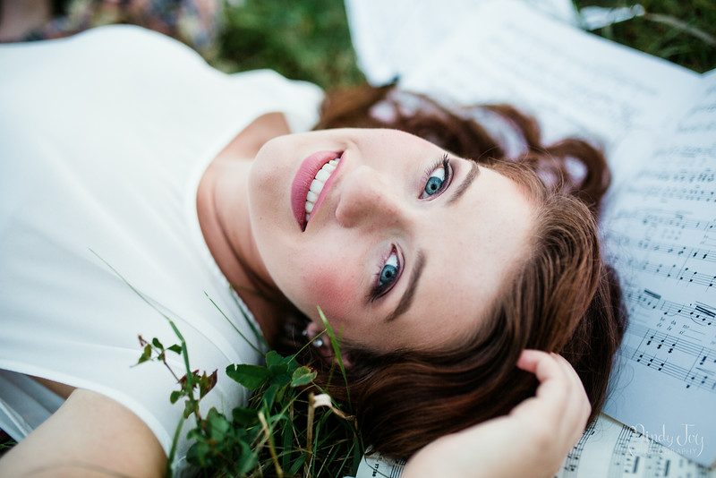 Senior portraits Laying in the Grass with Music Sheets