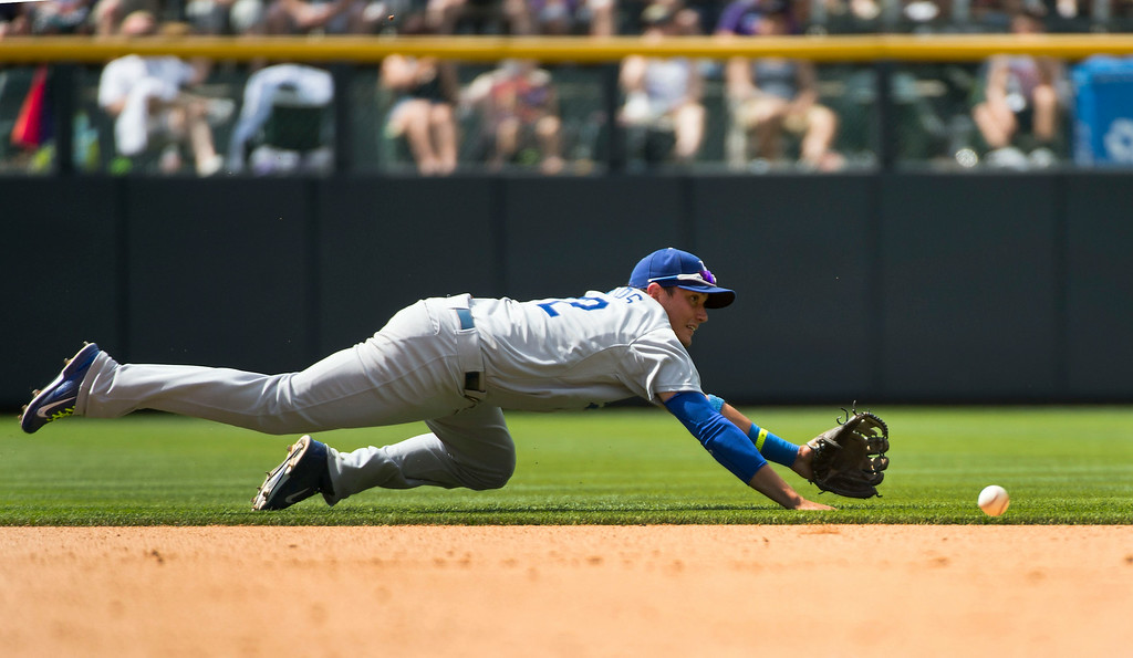 . Los Angeles Dodgers shortstop Miguel Rojas (72) dives after a hard hit by Colorado Rockies center fielder Drew Stubbs (13) during the fourth inning July 6, 2014 at Coors Field. Rojas couldn\'t make the play. (Photo by John Leyba/The Denver Post)