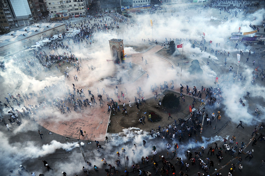 . People run away as Turkish riot policemen fire tear gas on Taksim square on June 11, 2013. Turkish police fired massive volleys of tear gas and jets of water to disperse thousands of anti-government demonstrators in Istanbul\'s Taksim Square on June 11, after earlier apparently retreating.  BULENT KILIC/AFP/Getty Images