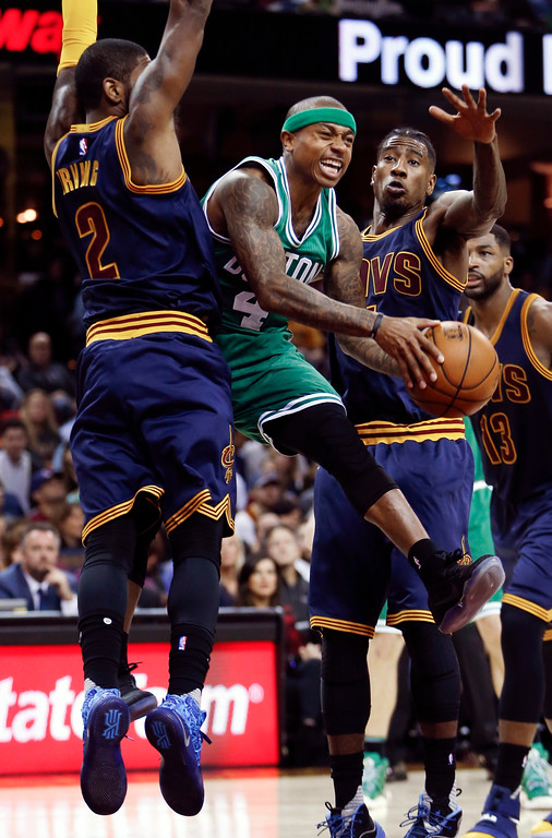 . Boston Celtics\' Isaiah Thomas (4) looks to pass between Cleveland Cavaliers\' Kyrie Irving (2) and Iman Shumpert during the first half of an NBA basketball game Thursday, Nov. 3, 2016, in Cleveland. (AP Photo/Ron Schwane)