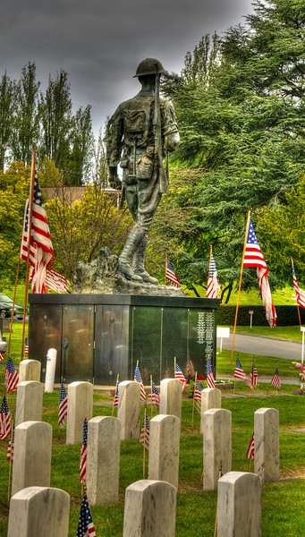"""11 Nov 11.  With Friday being Veteran's Day, I share this image of the WWI Doughboy which stands prominently at the """"y"""" in the road dividing the two halves of Seattle's Washelli Cemetery reserved for American Veterans and dedicate it to those who gave their all to the country. To which I wish to add my insignificant thanks for all those veterans, no matter how long they served, for all their sacrifices! The image appears slanted but it isn't, the statue and graves are on a little hillside sloping downward to the right. It is tonemapped (HDR), gritty, and intentionally dark; that is the mood I wanted to impart. ISO 200; 1/321 sec @ f / 13 (middle of 5)."""