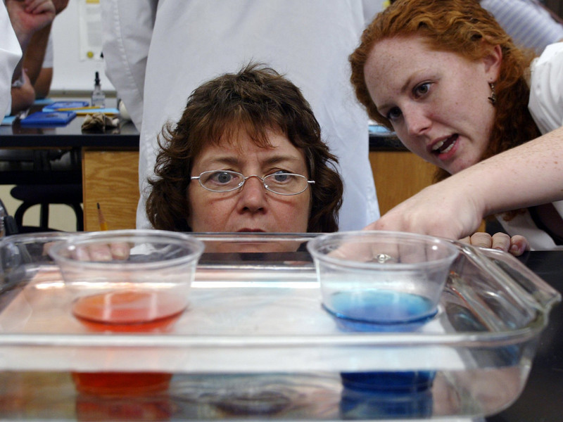 Heide Hatcher (left) takes a peak at two beakers as she listen to Joy Boone (right) describe the different speeds of hot water (bottom left) and cold water (bottom right) during a two-week Hands-on Science Lab program of continuing education for science teachers in the Physical Science building at Chico State campus Tuesday. - halley photo 6/27/06