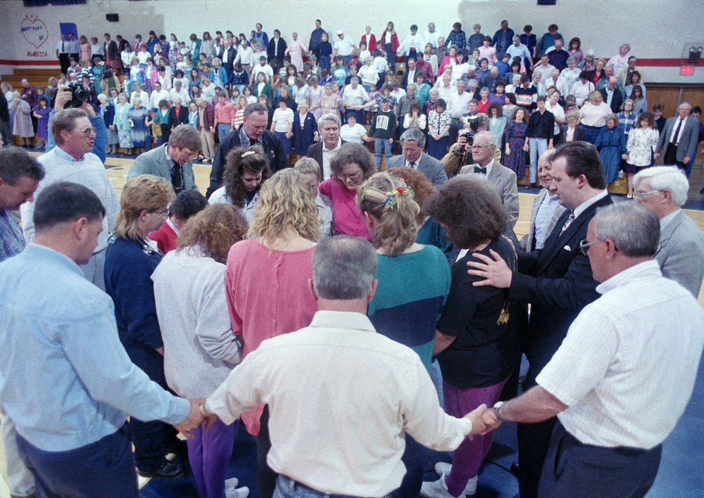 . An inner circle of wives of prison guards is surrounded by a ring of ministers during a prayer service in Lucasville, Ohio, April 14, 1993. The service was for guards at the Southern Ohio Correctional Facility, where rioting inmates have taken eight guards hostage and killed seven other inmates. (AP Photo/Al Behrman)