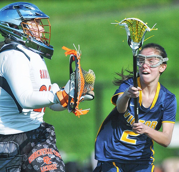 Jack Haley/Messenger Post MediaChurchville-Chili keeper Paulina Goodemote looks to clear the ball as Victor's katie Kopp applies the presure during the Saints 11-7 home win over Victor on Monday.