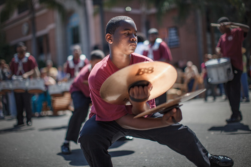 A young teenager holding two cymbals on each hand.