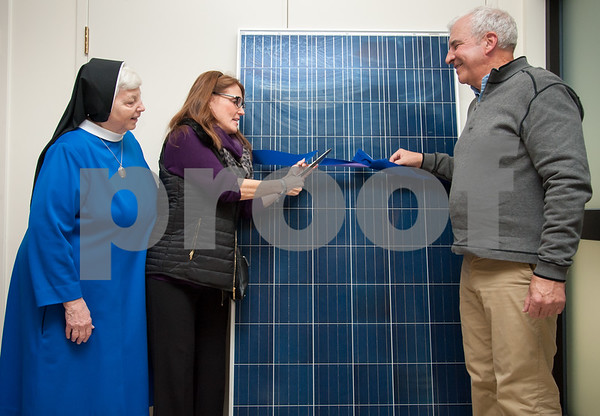 401/09/18 Wesley Bunnell | Staff The Daughters of Mary of the Immaculate Conception presented certificates of appreciation to several businesses for their help in installing solar panels on all of their buildings. Mother Jennifer, L, looks on as Karen Kulak from Associated Real Estate Servies and John O'Brien of EcoSolar LLC cut the ceremonial ribbon on a sample solar panel.