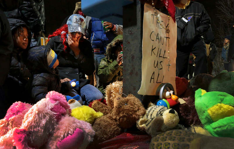. Courtney Palmer, center left, a cousin of Antonio Martin, mourns the loss at a growing memorial in a gas station parking lot in Berkeley, Mo., Wednesday, Dec. 24, 2014. The mayor of the St. Louis suburb of Berkeley urged calm Wednesday after a white police officer killed the black 18-year-old who police said pointed a gun at him, reigniting tensions that have lingered since the death of Michael Brown in neighboring Ferguson. (AP Photo/St. Louis Post-Dispatch, Robert Cohen)