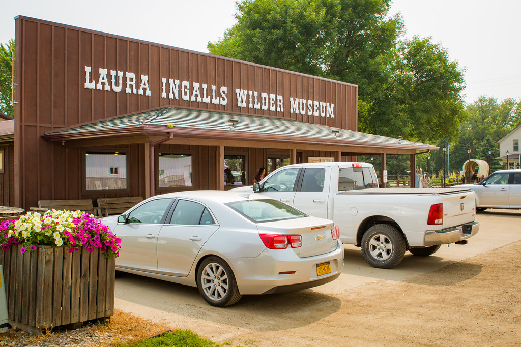 Cars are parked in front of a wooden building with letters that say 'Laura Ingalls Wilder Museum'.