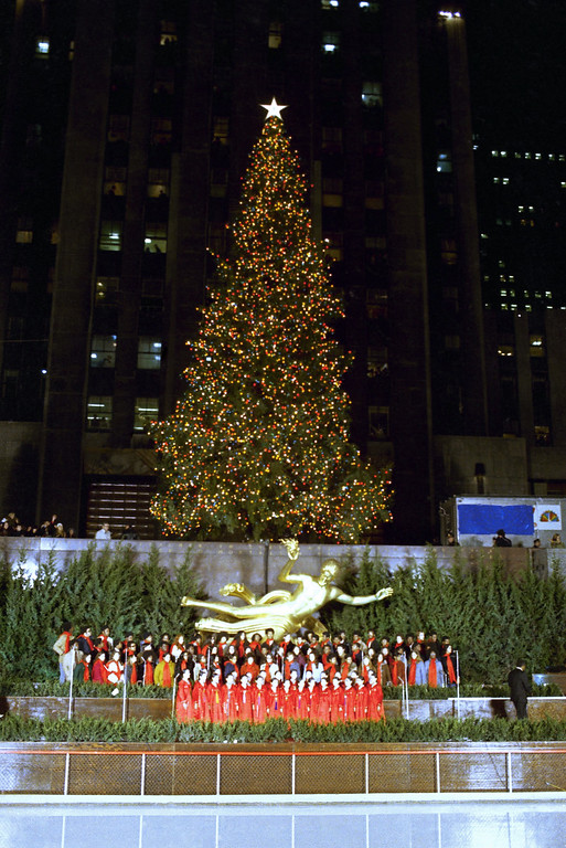 . Carols are sung beneath the illuminated Christmas tree in New York\'s Rockefeller Plaza, USA in 1971. (AP Photo)