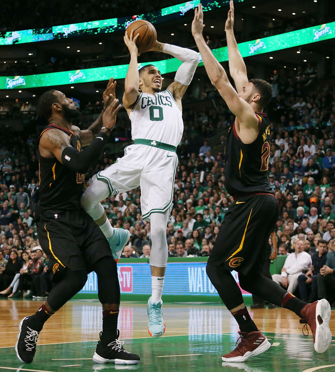 . Boston Celtics forward Jayson Tatum, center, drives between Cleveland Cavaliers forwards LeBron James, left, and Larry Nance Jr., right, during the second half in Game 7 of the NBA basketball Eastern Conference finals, Sunday, May 27, 2018, in Boston. (AP Photo/Elise Amendola)
