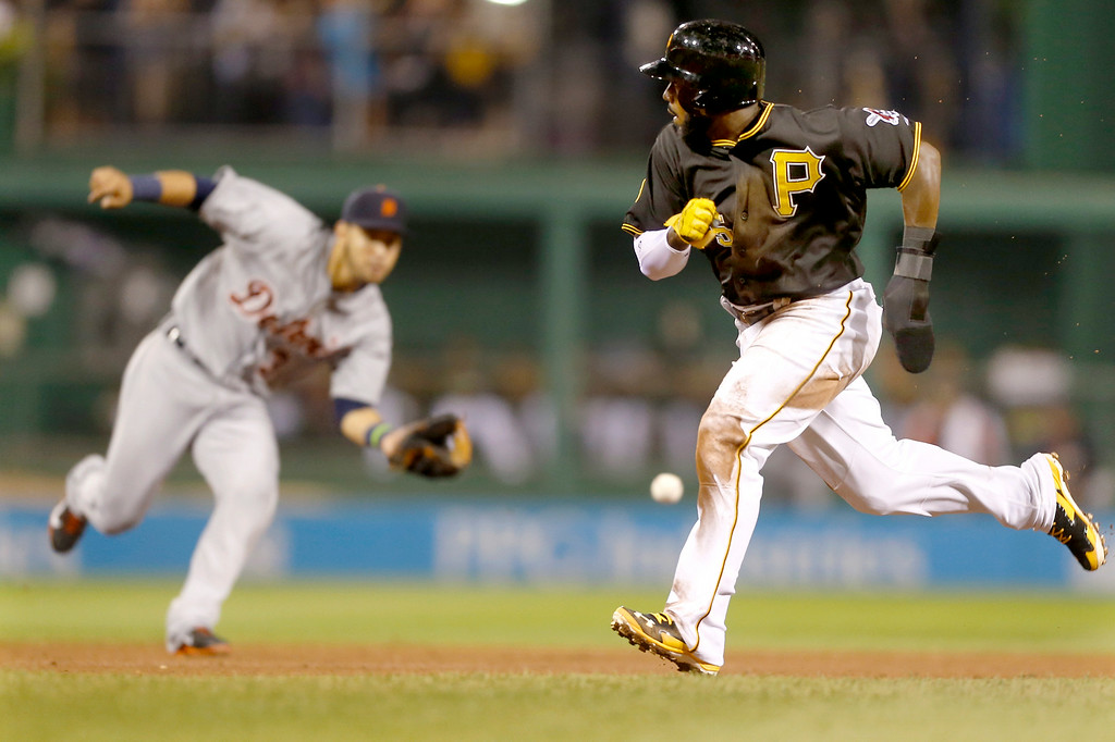 . Pittsburgh Pirates\' Josh Harrison, right, heads for third as Detroit Tigers shortstop Eugenio Suarez fields a ground ball by Jordy Mercer who was out on the fielders choice in the fifth inning of the baseball game on Tuesday, Aug. 12, 2014, in Pittsburgh. (AP Photo/Keith Srakocic)