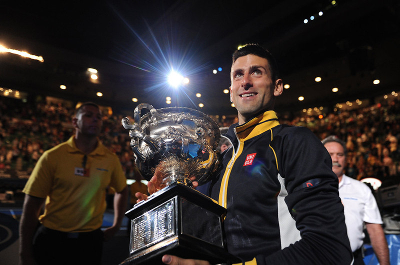 . Serbia\'s Novak Djokovic carries his trophy around Rod Laver Arena after defeating Britain\'s Andy Murray in the men\'s final at the Australian Open tennis championship in Melbourne, Australia, Monday, Jan. 28, 2013. (AP Photo/Andrew Brownbill)