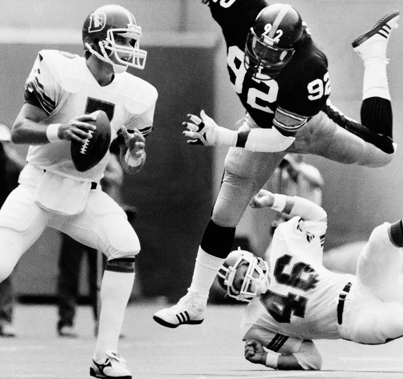 . Rookie Denver Bronco quarterback John Elway, left, gets some high flying heat from Pittsburgh Steeler defensive end Keith Gary, (92), as Broncos? Dave Preston, (46), fails to make the stop during the season opener, Sunday, Sept. 5, 1983, Pittsburgh, Pa. Elway played only the first half, completing one pass out of eight for 14 yards, but the Broncos won the game 14-10 under the leadership of Veteran quarterback Steve DeBerg. (AP Photo/Keith Srakocic)