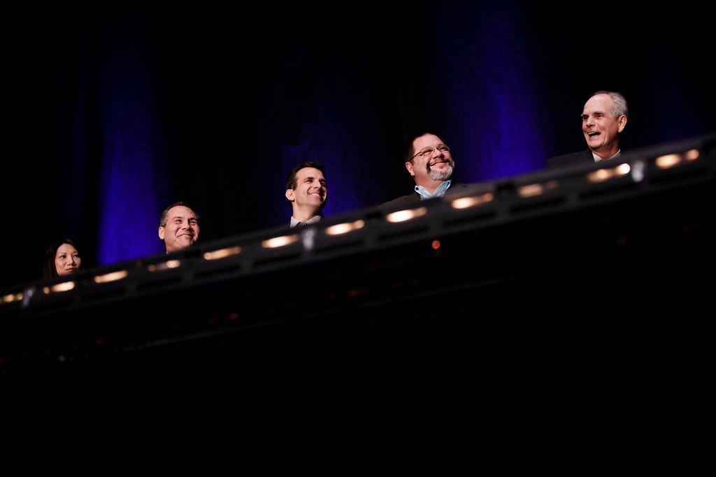 . From left, San Jose City Council members, Madison Nguyen, Xavier Campos, Sam Liccardo, Pete Constant and Mayor Chuck Reed are seen behind stage light fixtures as they react to CEO of Silicon Valley Leadership Group, Carl Guardino\'s introduction of Reed\'s role as mayor, before Reed\'s annual state of the city speech at the San Jose Civic Auditorium on Feb. 7, 2013. (Dai Sugano/Staff)