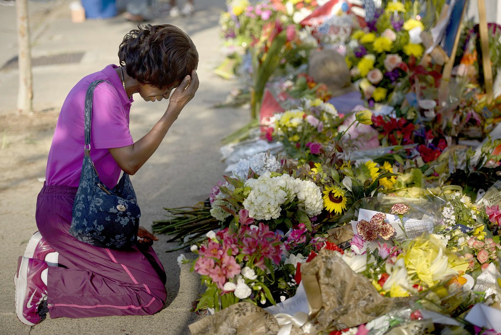 . Patricia Bailey says a prayer at a memorial outside Emanuel AME Church June 20, 2015 in Charleston, South Carolina.Thousands of mourners clutching red and white roses attended a vigil in the stunned city of Charleston Friday to remember nine African-American men and women shot dead by a suspected white supremacist. AFP PHOTO/BRENDAN SMIALOWSKI/AFP/Getty Images