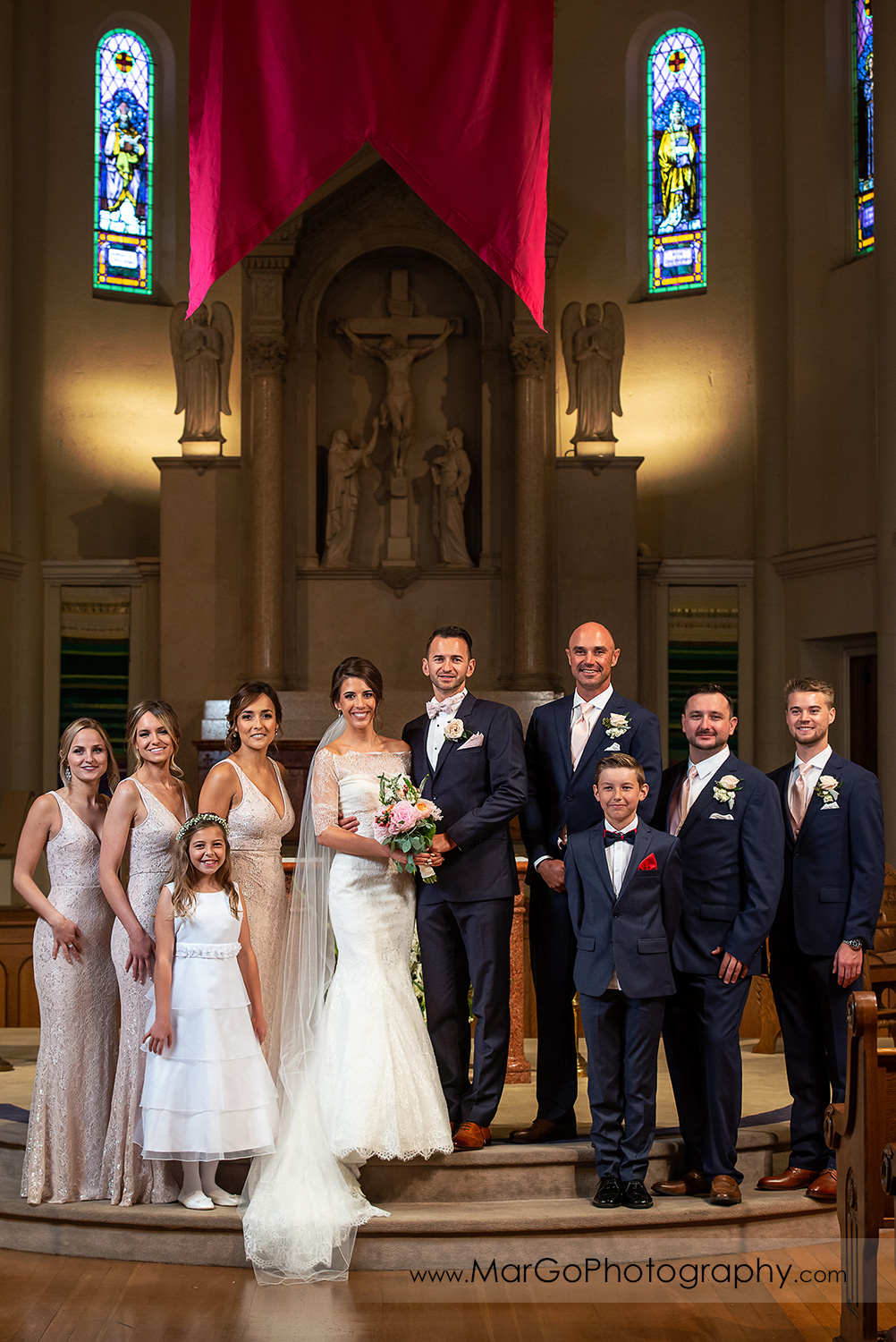 bridal party portrait in front of altar at Oakland Church of Saint Leo the Great