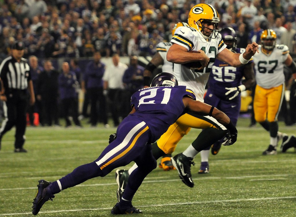 . Minnesota cornerback Josh Robinson grabs the legs of Green Bay quarterback Aaron Rodgers in the first quarter. (Pioneer Press: John Autey)