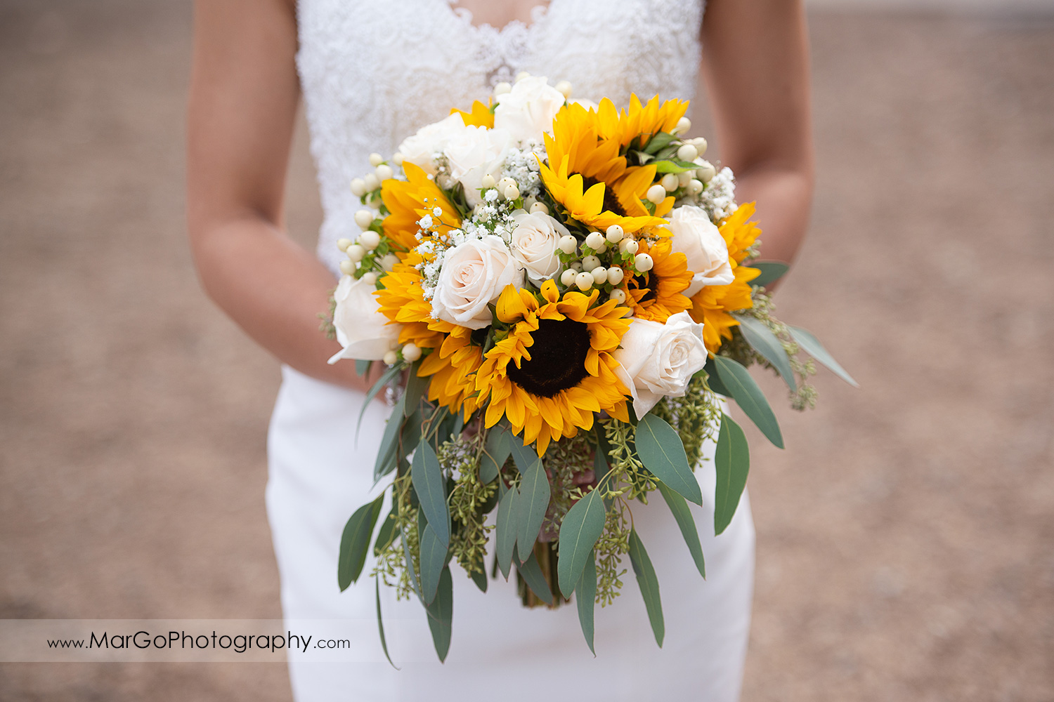 yellow and white flowers bouquets held by bride at Long Branch Saloon & Farms in Half Moon Bay